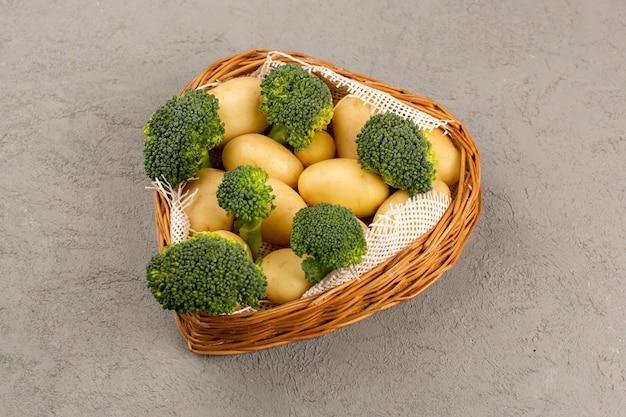 Vista superior de papas y brócoli pelado verde dentro de la canasta en el piso gris