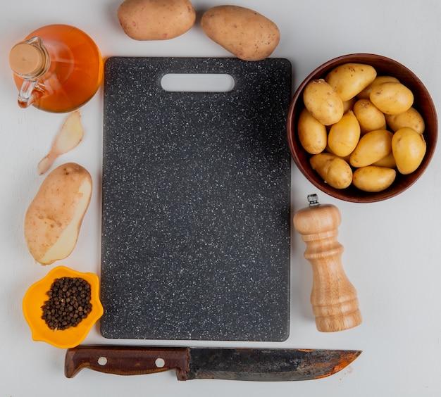 Vista superior de papas con cáscara de mantequilla, pimienta negra, sal y cuchillo alrededor de la tabla de cortar en blanco