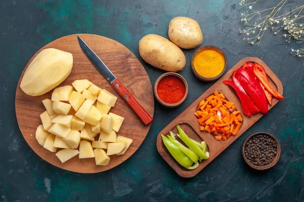 Vista superior de papas frescas en rodajas con condimentos y pimientos en rodajas en el escritorio azul oscuro