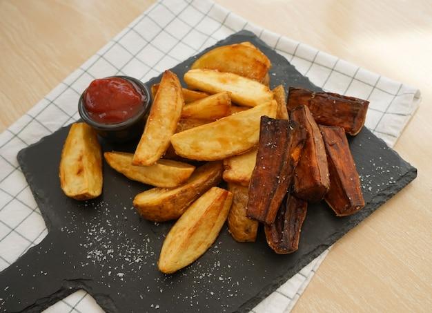 Vista superior de papas fritas y batatas horneadas en una placa de pizarra negra cortada con salsa de tomate
