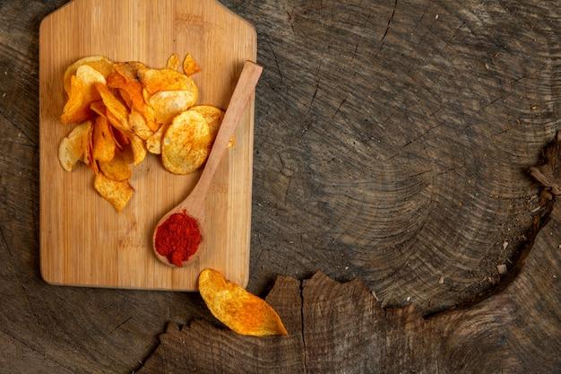 Vista superior de papas fritas con una cuchara de madera de chile en polvo sobre una tabla para cortar madera con espacio de copia