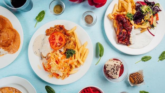 Vista superior de papas fritas con ensaladas, carne asada y salsas en la mesa
