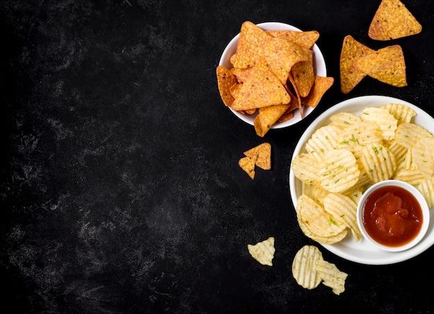 Vista superior de papas fritas y nacho chips con salsa de tomate