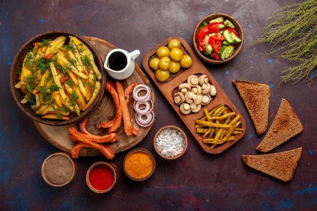 Vista superior de papas fritas con panes de pan de condimentos y diferentes verduras en la superficie oscura
