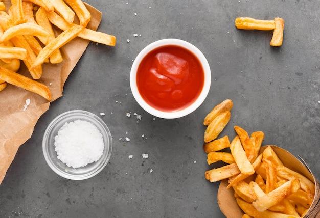 Vista superior de papas fritas en papel con sal y salsa de tomate