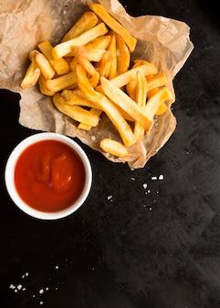 Vista superior de papas fritas saladas con salsa de tomate