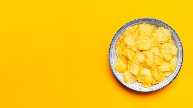 vista superior de papas fritas sobre fondo amarillo