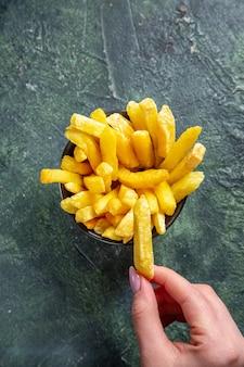 Vista superior de papas fritas en superficie oscura