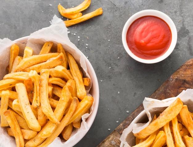 Vista superior de papas fritas en un tazón con salsa de tomate