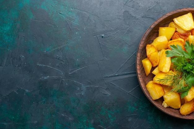Vista superior de papas en rodajas cocidas con verduras dentro de la placa marrón en el escritorio azul oscuro