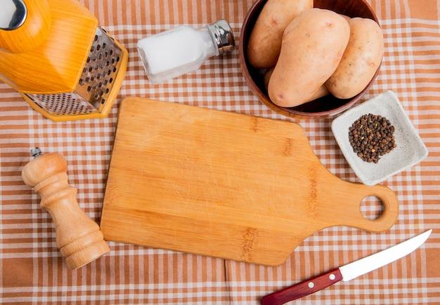 Vista superior de papas en un tazón con cuchillo de rallador de sal de pimienta negra alrededor de la tabla de cortar sobre fondo de tela escocesa