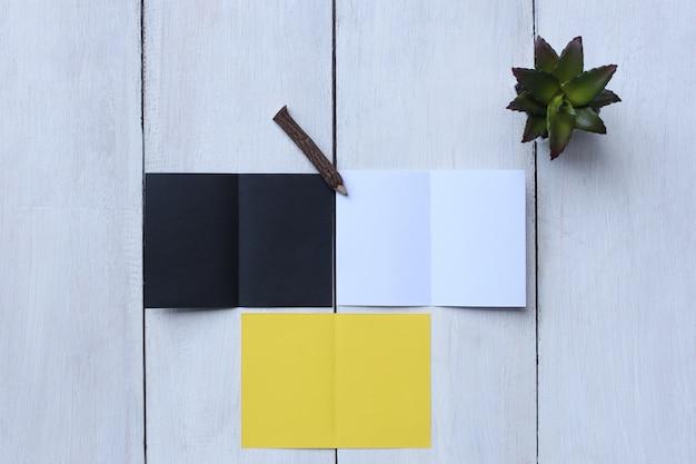 Vista superior de papel amarillo, papel blanco, papel negro, lápiz y maceta en el piso de madera blanco