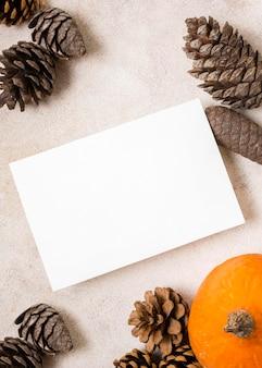 Vista superior del papel en blanco con conos de pino otoñal