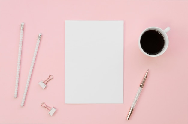 Vista superior de papel en blanco con lápices y taza de café