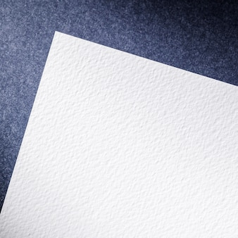 Vista superior de papel blanco sobre fondo azul.