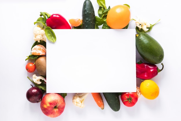 Vista superior de papel en blanco sobre verduras y frutas frescas sobre fondo blanco
