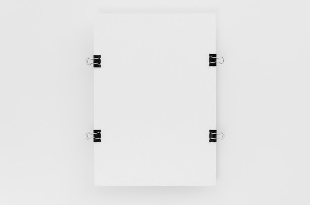 Vista superior de papel con clips metálicos en los lados.