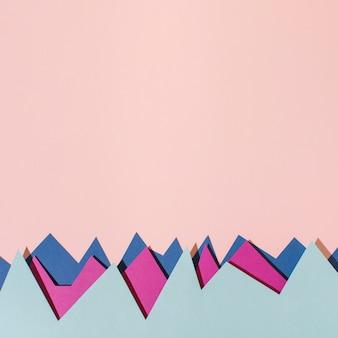 Vista superior de papel de colores sobre fondo rosa