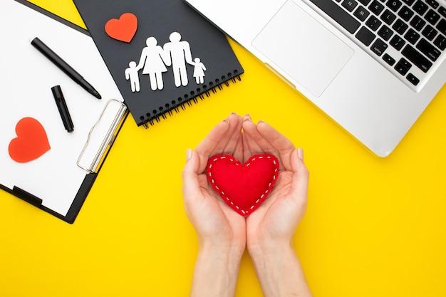 Vista superior papel cortado familia y manos sosteniendo corazón