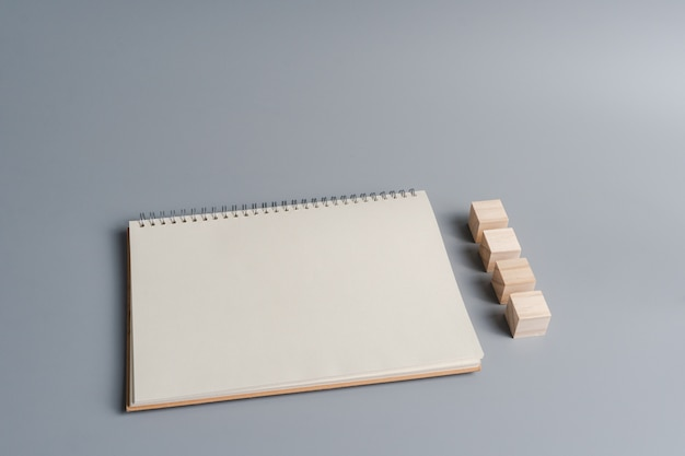 Vista superior del papel de cuaderno en blanco, bloque de cubo de madera para crear signos, símbolos o letras