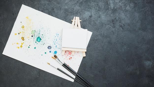 Vista superior de papel dibujado manchado con pincel y mini caballete en blanco