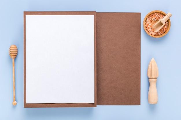 Vista superior del papel de menú en blanco con cucharón de miel y cuchara