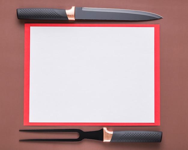 Vista superior del papel de menú en blanco con cuchillo y tenedor