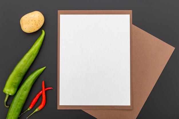 Vista superior del papel de menú en blanco con pimientos y papas