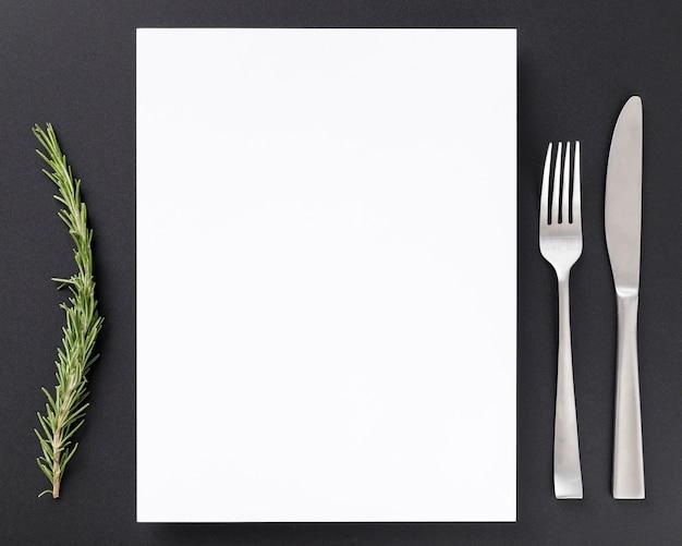 Vista superior del papel de menú en blanco con pino y cubiertos