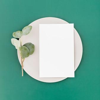 Vista superior del papel de menú en blanco en placa con planta