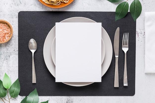 Vista superior del papel de menú en blanco en un plato con cubiertos y hojas