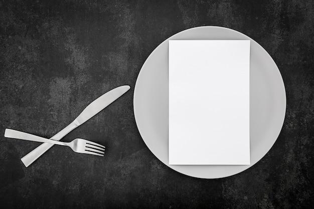 Vista superior del papel de menú en blanco con plato y cubiertos