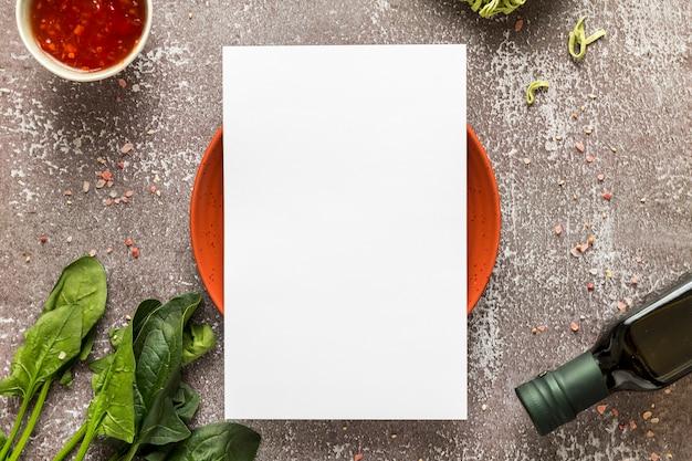 Vista superior del papel de menú en blanco en un plato con espinacas y aceite de oliva