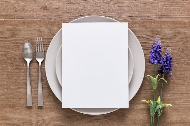 Vista superior del papel de menú en blanco en un plato con flores y cubiertos