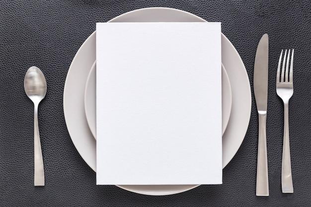 Vista superior del papel de menú en blanco en un plato con tenedor y cuchillo