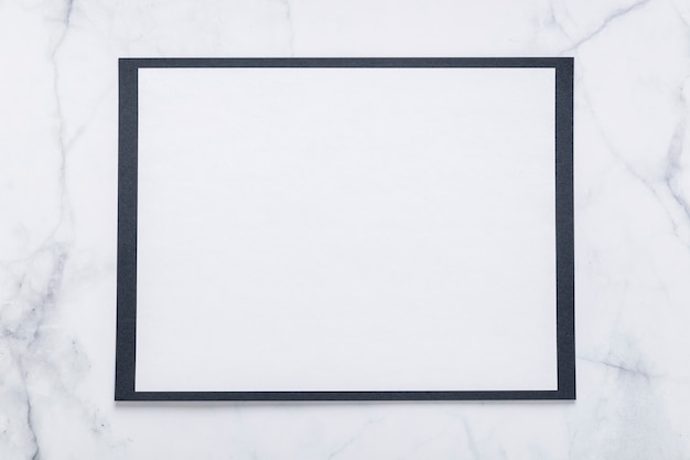 Vista superior del papel de menú en blanco sobre superficie de mármol