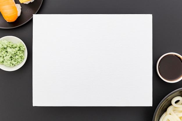 Vista superior del papel de menú en blanco con sushi y salsa de soja