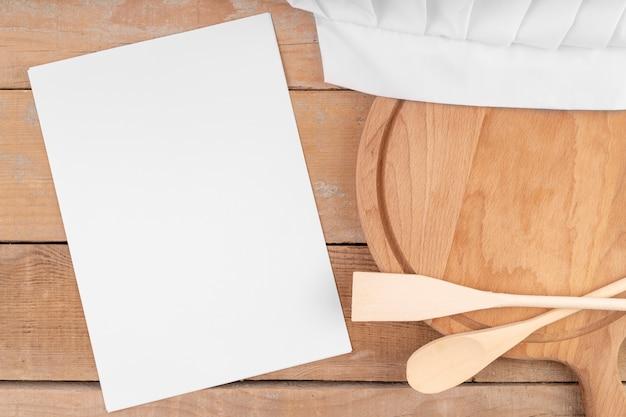Vista superior del papel de menú vacío con cucharas de madera