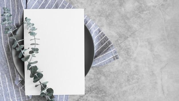 Vista superior del papel de menú vacío en placa con hojas y espacio de copia