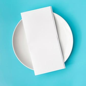 Vista superior del papel de menú vacío en plato blanco