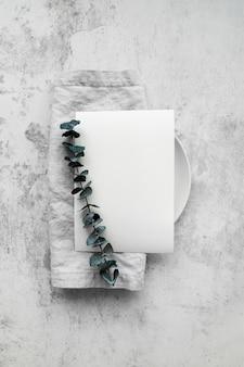 Vista superior del papel de menú vacío en plato con hojas