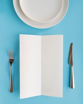 Vista superior del papel de menú vacío con platos y cubiertos