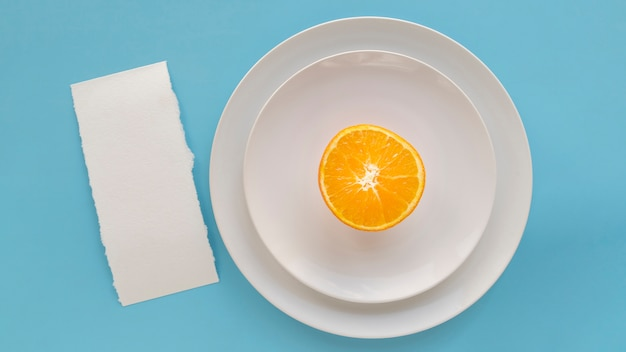 Vista superior del papel de menú vacío con platos y naranja