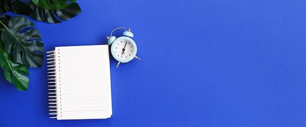 Vista superior del papel de nota en blanco, reloj despertador y hoja de monstera sobre fondo azul.