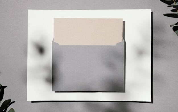 Vista superior del papel de papelería con plantas y sobres.