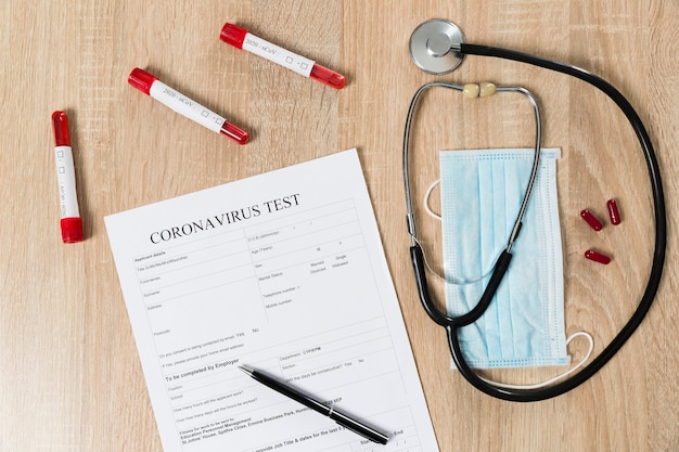 Vista superior del papel de prueba de coronavirus con estetoscopio y pastillas