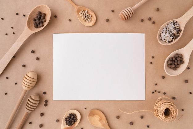 Vista superior de papel vacío con cucharas de madera y condimentos.