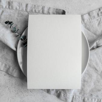 Vista superior de papel vacío en plato con tela