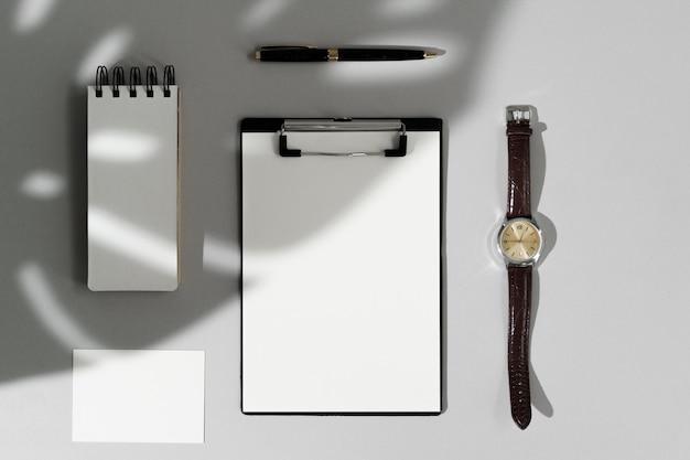 Vista superior de papelería en blanco, reloj y bolígrafo sobre fondo gris