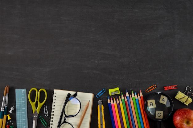 Vista superior de papelería o útiles escolares con libros, lápices de colores, calculadora, computadora portátil, clips y manzana roja sobre fondo de pizarra.